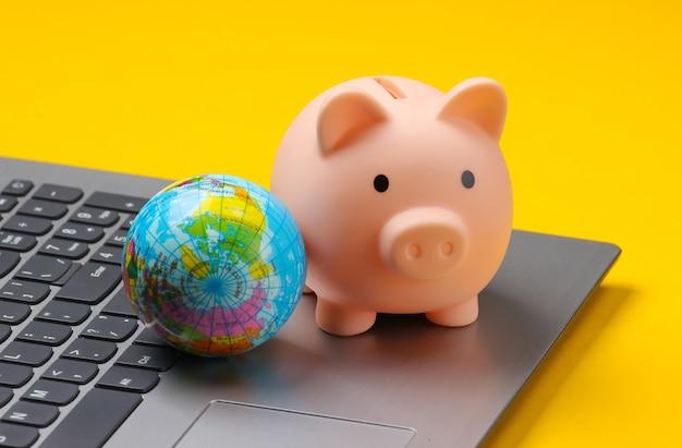 Cofrinho com globo no teclado do laptop, amarelo.