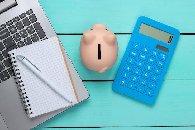 Cofrinho com laptop, calculadora, caderno na superfície de madeira azul. ganhar dinheiro online ou conceitos de negócios na internet. vista do topo. postura plana