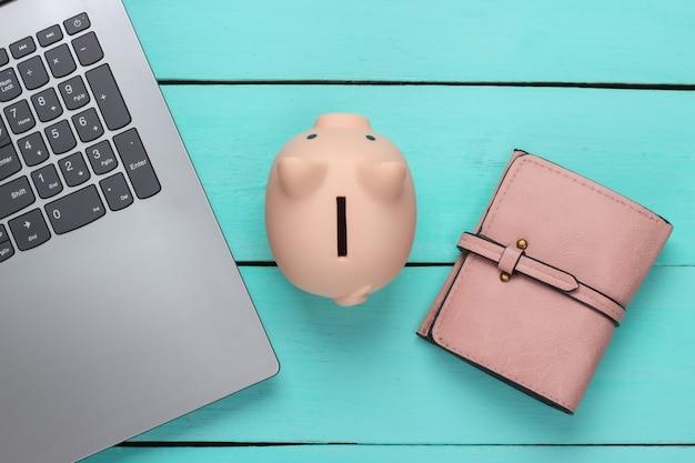 Cofrinho com laptop, carteira na superfície de madeira azul. ganhar dinheiro online ou conceitos de negócios na internet. vista do topo. postura plana