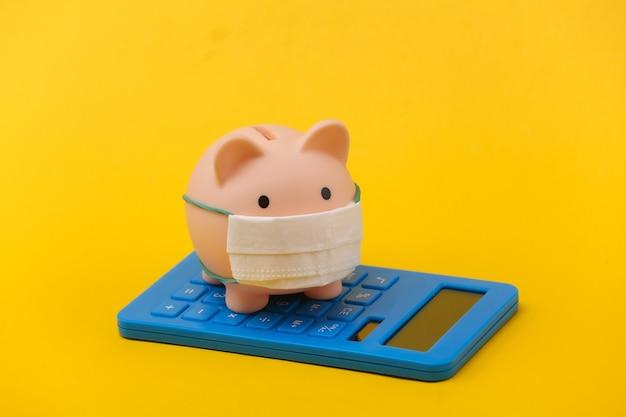 Cofrinho com máscara médica e calculadora em fundo amarelo. doença econômica. crise financeira. pandemia do covid-19