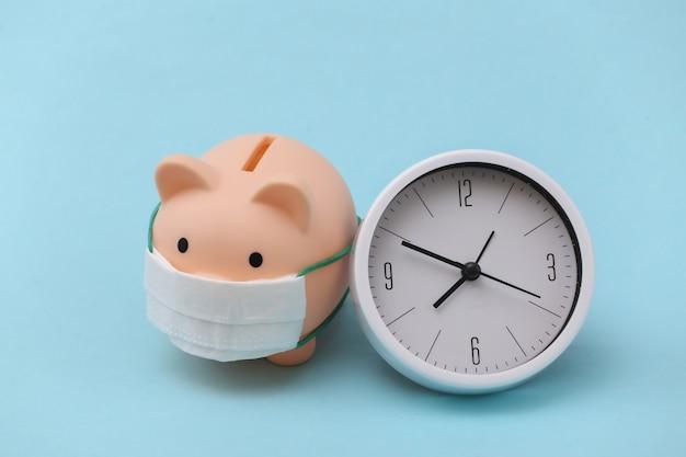 Cofrinho com máscara médica e relógio sobre fundo azul. doença econômica. crise financeira. pandemia do covid-19