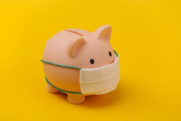 Cofrinho com máscara médica em fundo amarelo. doença econômica. crise financeira. pandemia do covid-19