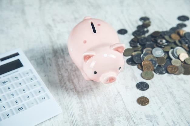 Cofrinho com moedas e calculadora na mesa