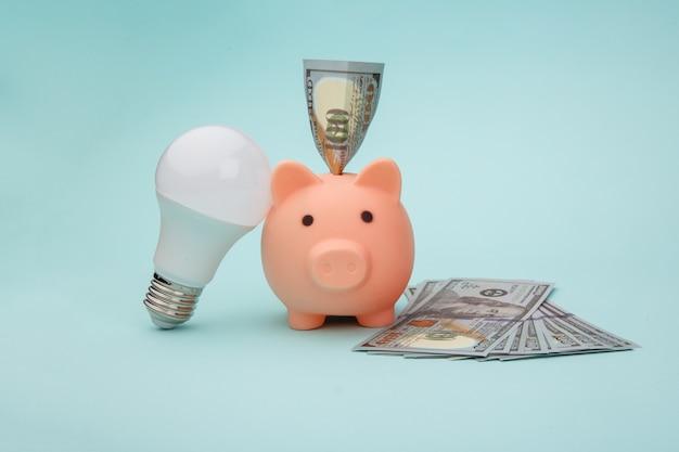 Cofrinho com notas de dinheiro de dólar e lâmpada sobre fundo azul. conceito de economia de energia