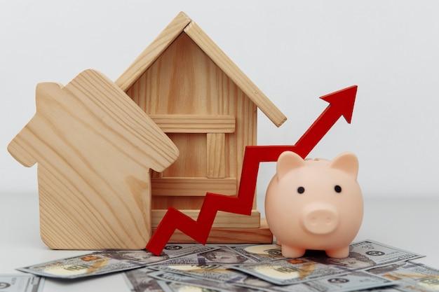 Cofrinho com seta para cima e modelos de casa em notas de dólar economizando ou emprestando para comprar casa ou conceito de proprietário imobiliário