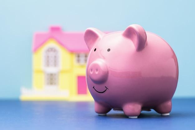 Cofrinho de cerâmica e uma casa de brinquedo em um fundo colorido o custo da habitação