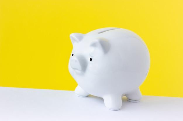 Cofrinho de porco branco sobre um fundo amarelo brilhante. conceito minimalista