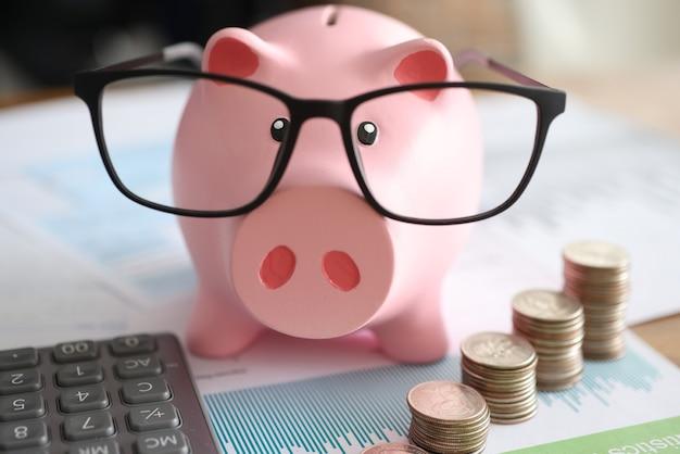 Cofrinho de porco rosa em copos perto de moedas e gráficos de negócios