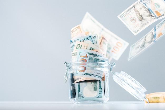Cofrinho de vidro cheio de dinheiro. as notas estão espalhadas de cima. o conceito de esbanjamento