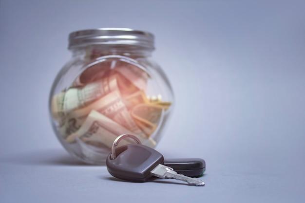 Cofrinho de vidro com dólares e chaves do carro em uma parede de luz com efeito brilhante. dinheiro reservado para comprar um carro.