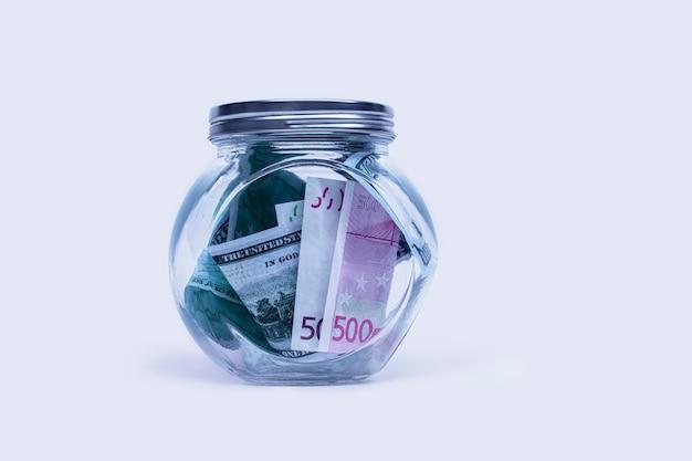 Cofrinho de vidro com dólares e euros em um fundo branco.