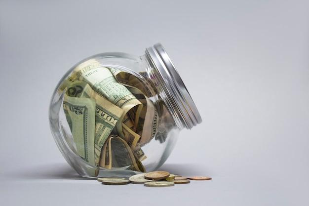 Cofrinho de vidro com dólares e euros em um fundo cinza.