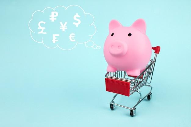 Cofrinho dentro do carrinho de compras com moedas do mundo do holograma digital do holograma na nuvem pensada acima de sua cabeça sobre fundo azul. o conceito de economizar dinheiro nas compras.