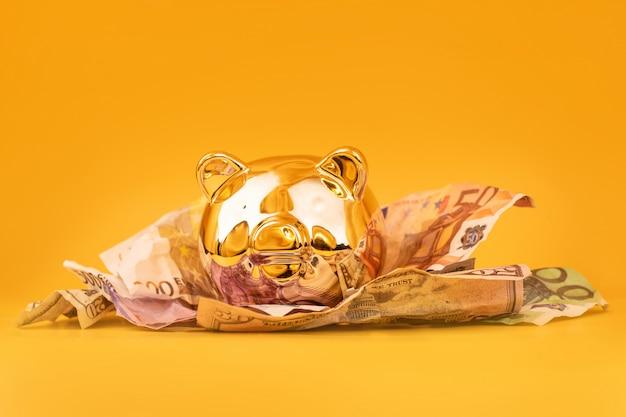 Cofrinho dourado com dinheiro, notas de euro e dólar
