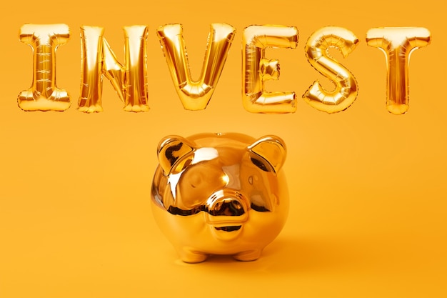 Cofrinho dourado sobre fundo amarelo com a palavra dourada investir feito de balões infláveis de folha. conceito de investimento e bancário. economia de dinheiro, caixa de dinheiro, finanças, investimentos.