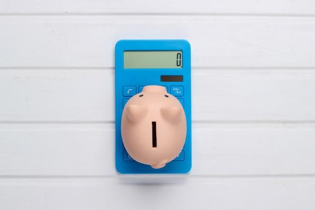 Cofrinho e calculadora azul na superfície de madeira branca. vista do topo