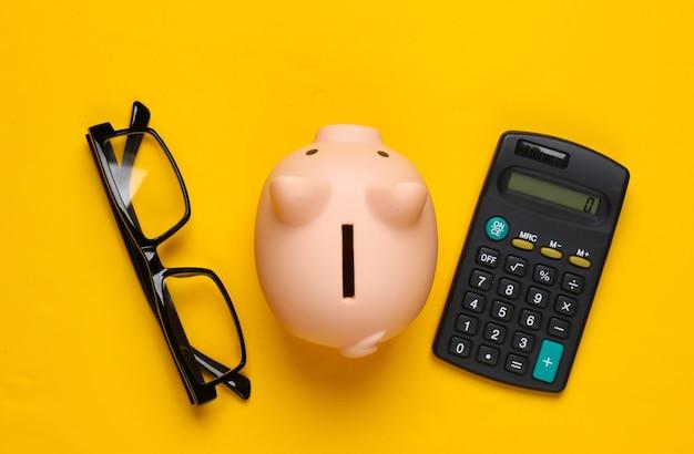 Cofrinho e calculadora azul, óculos amarelo
