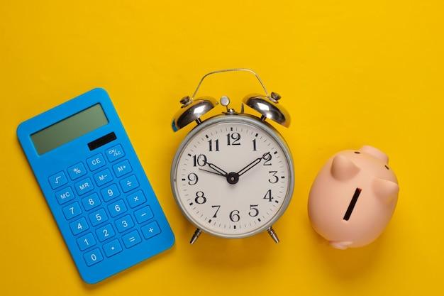Cofrinho e despertador, calculadora azul em amarelo