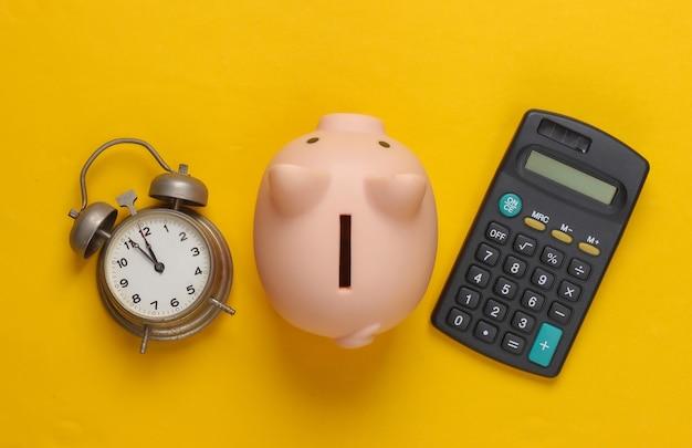Cofrinho e despertador, calculadora em amarelo