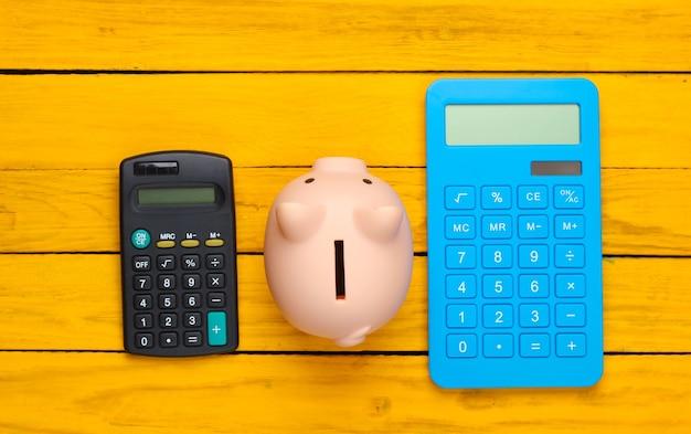 Cofrinho e duas calculadoras em uma superfície de madeira amarela. vista do topo