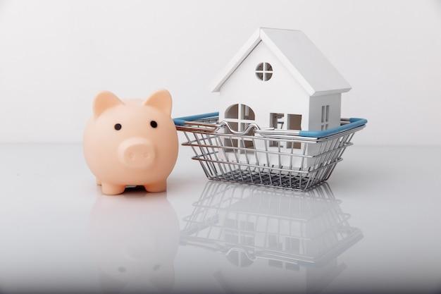 Cofrinho e modelo de casa na cesta de compras