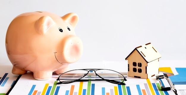 Cofrinho e modelo de casa para finanças e conceito bancário na superfície do gráfico