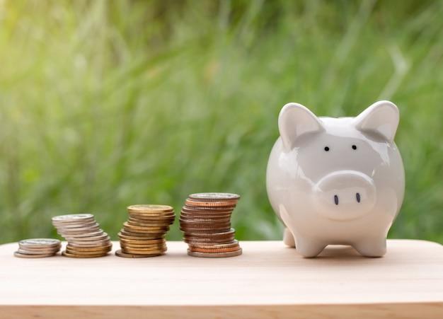 Cofrinho e moeda de prata colocados na mesa de madeira no fundo natural conceito de negócios e economia