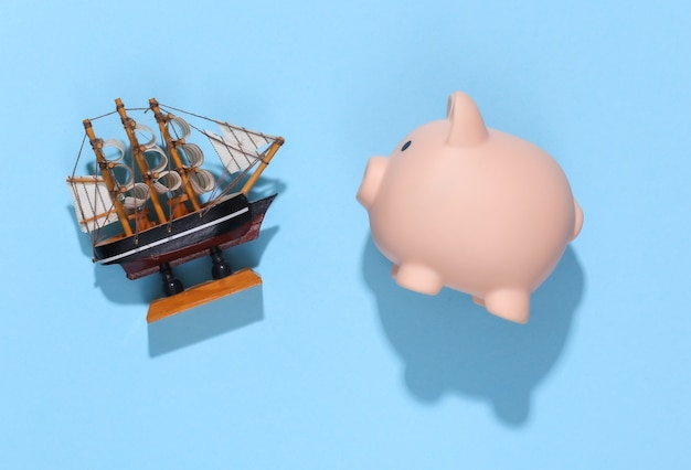 Cofrinho e navio em azul brilhante ensolarado. planejamento de viagens.