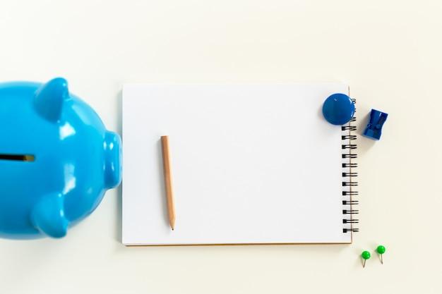 Cofrinho e o bloco de notas em uma tabela