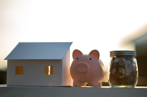 Cofrinho e um modelo de casa, conceito economizando dinheiro para casa e imóveis.