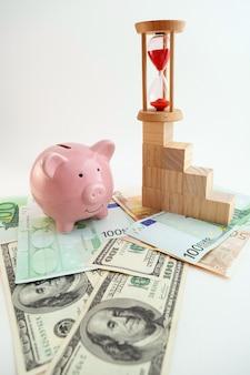 Cofrinho em forma de porco, ampulheta, cubos de madeira de gráfico crescente, notas de euro e dólares americanos em fundo branco isolado