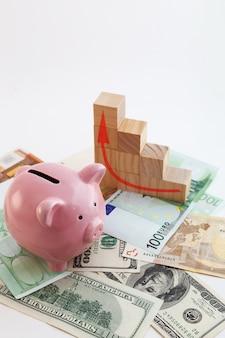 Cofrinho em forma de porco, cubos de madeira de gráfico crescente, notas de euro e dólares americanos em fundo branco isolado