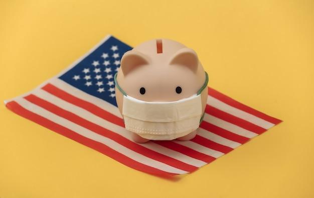 Cofrinho em máscara médica com a bandeira dos eua em fundo amarelo. pandemia covid-19
