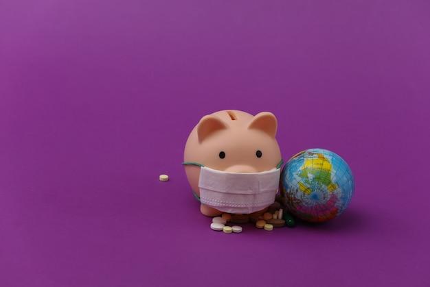 Cofrinho em máscara médica com globo, comprimidos sobre fundo roxo. pandemia do covid-19