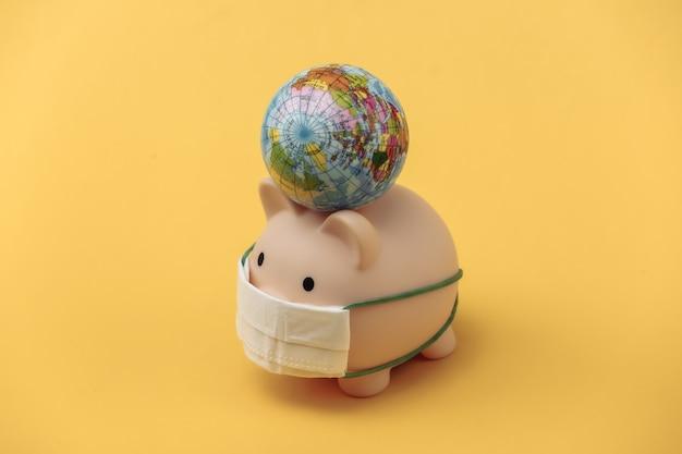 Cofrinho em máscara médica com globo em fundo amarelo. pandemia do covid-19