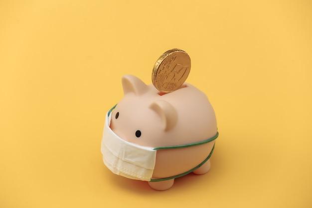 Cofrinho em máscara médica com moedas em fundo amarelo. doença econômica. crise financeira. pandemia do covid-19