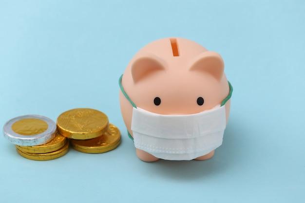 Cofrinho em máscara médica com moedas sobre fundo azul. doença econômica. crise financeira. pandemia do covid-19