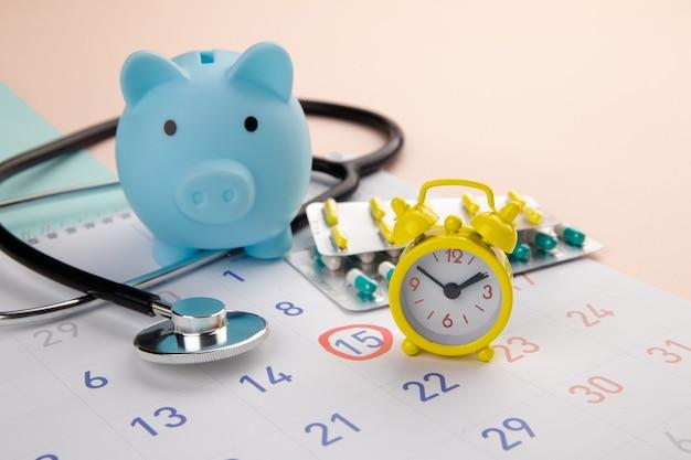 Cofrinho, estetoscópio, despertador e calendário em uma mesa, cronograma para verificar o conceito saudável