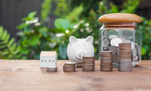Cofrinho, moedas de dinheiro e modelo de casa na mesa de madeira com a natureza no conceito de poupança e investimento