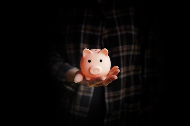 Cofrinho na mão de uma mulher. economizando o conceito de dinheiro.