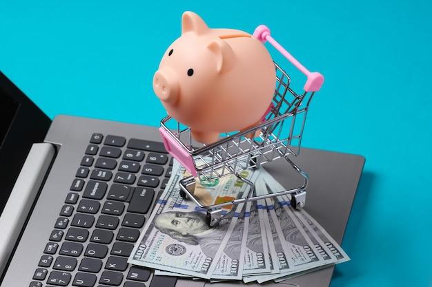 Cofrinho no carrinho de compras com notas de 100 dólares no teclado do laptop close-up