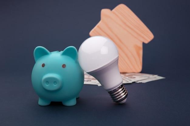 Cofrinho, notas de dinheiro e lâmpada led