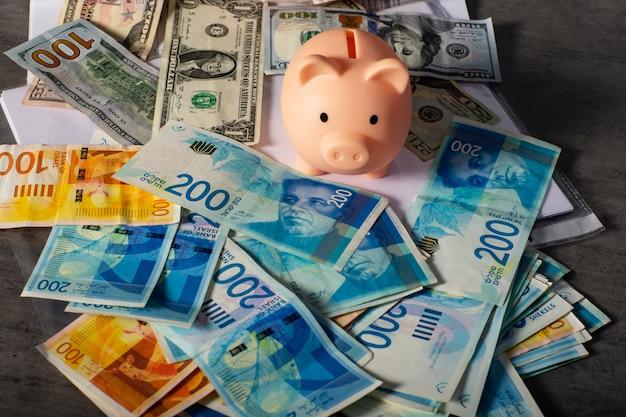 Cofrinho para economizar dinheiro com notas de novos shekels israelenses e dólares está em cima da mesa. piggybank por economizar dinheiro e documentos comerciais na mesa com dinheiro americano e israelense na mesa cinza