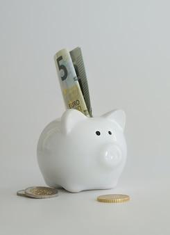 Cofrinho para economizar dinheiro. riqueza, orçamento, investimento, conceito de finanças. caixa de dinheiro, cofrinho em fundo branco.