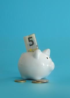 Cofrinho para economizar dinheiro. riqueza, orçamento, investimento, conceito de finanças. caixa de dinheiro, cofrinho sobre o fundo azul.