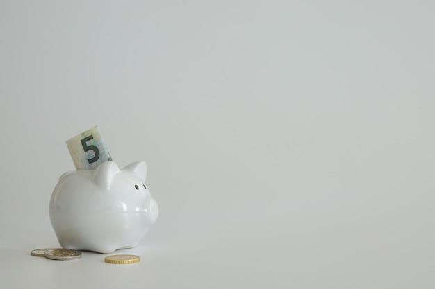 Cofrinho para economizar dinheiro. riqueza, orçamento, investimento, conceito de finanças. caixa de dinheiro, cofrinho sobre o fundo preto. espaço livre para texto, copie o espaço.