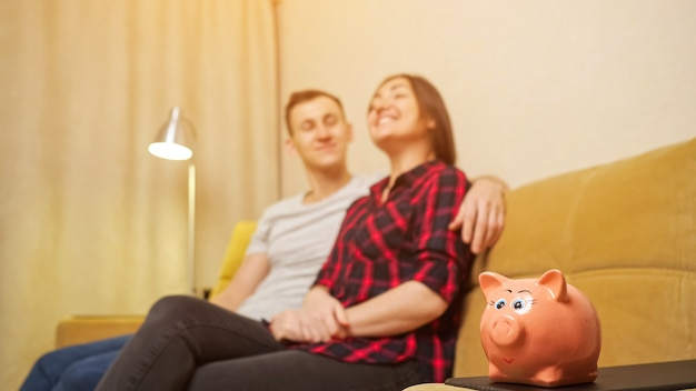 Cofrinho pequeno fica em cima da mesa contra jovem marido e mulher desfocados sentados no sofá amarelo e planejando a construção de uma casa nova vista de perto