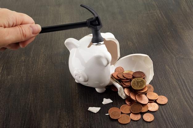 Cofrinho quebrado com dinheiro e moedas no fundo de madeira