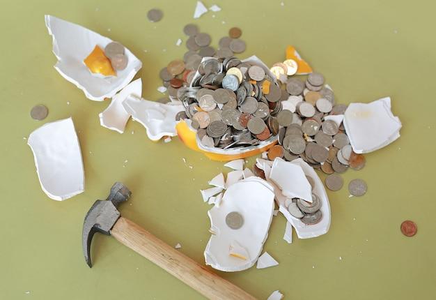 Cofrinho quebrado com martelo e moedas na mesa.