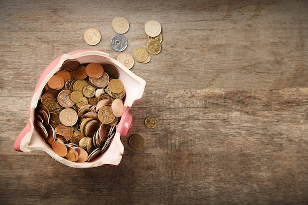 Cofrinho quebrado com moedas em fundo de madeira